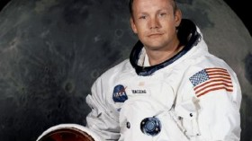 Portrait of Astronaut Neil A. Armstrong, commander of the Apollo 11 Lunar Landing mission in his space suit, with his helmet on the table in front of him. Behind him is a large photograph of the lunar