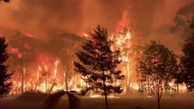 A fire blazes across bush as seen from Mount Tomah in New South Wales