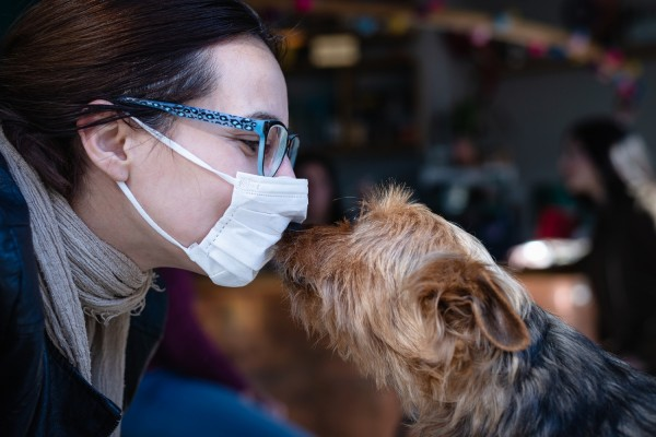 Woman with mask kissing dog.