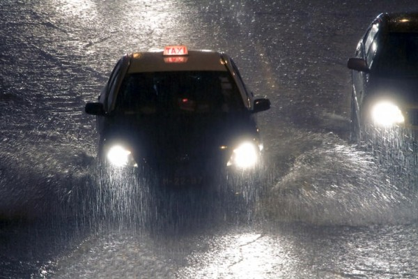 A taxi rides under heavy rain that is causing flooding in Macau, China