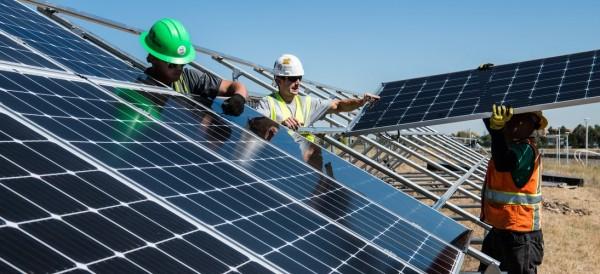 workers installing solar energy farm