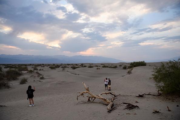 Visitors walk along sand dunes inside Death Valley National Park