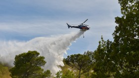 An helicopter drops its load of water to extinguish a fire