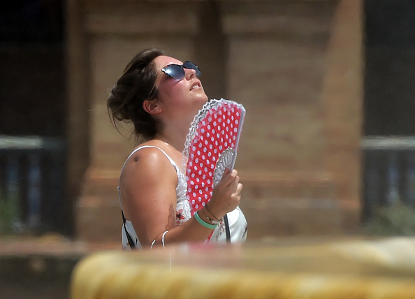 woman cools off faning herself due to the heat