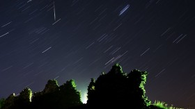 Perseid meteor crossing the night sky and stars trails