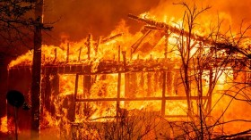 A home is consumed by flames as the Dixie fire rages on in Greenville, California