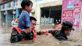 Rescuers evacuating a child from a flooded area after torrential rains in Suizhou