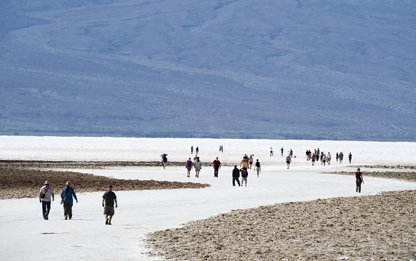 Visitors walk on the salt pan at Badwater Basin in Death Valley National Park