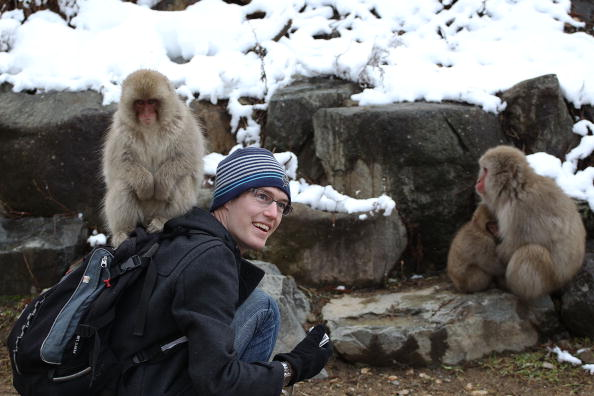 Visitor poses for a picture with Macaque monkeys
