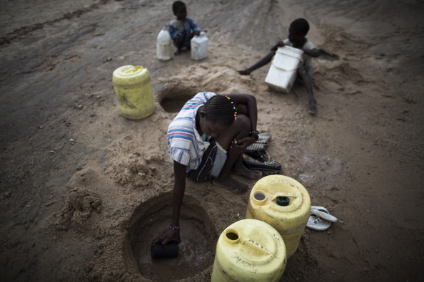 Woman scoops water from a dry river bed