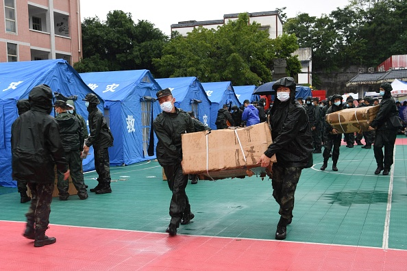 Rescuers transfer supplies near tents set up for people whose homes were damaged by the earthquake