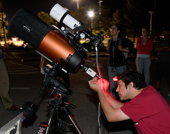 A person setting up a telescope to view asteroid