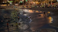 People enjoy an artificial beach after the sun goes down to avoid harmful ultraviolet rays that can cause skin cancer