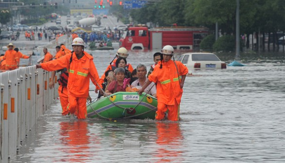 Fire workers transfer citizens with inflatable boat on flooded street