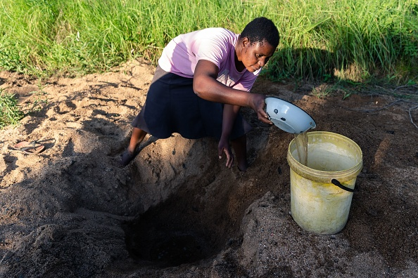 Woman scooping through sand in search of water
