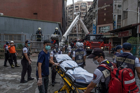 Paramedics transporting a dead body from a residential building in the wake of a fire